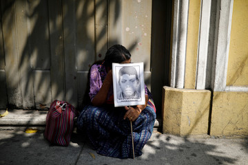A woman holds a picture of a missing person during a protest against a bill that would grant amnesty to war crimes committed during country's 36 year civil war outside the Congress, in Guatemala City