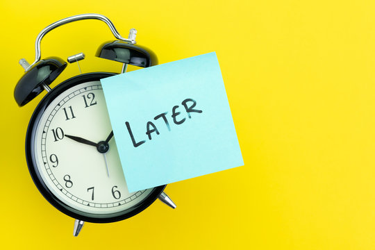 Sticky post with handwriting the word Later stick on alarm clock on solid yellow background with copy space using as procrastination, self discipline or laziness concept