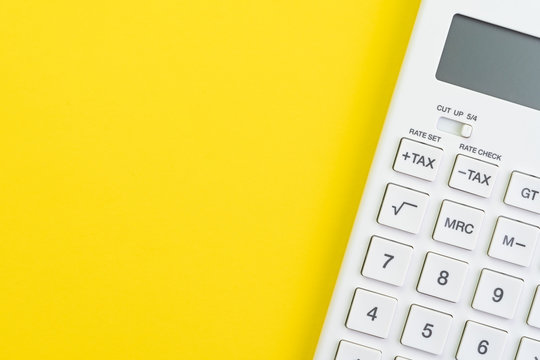 Mathematics, tax calculation, finance or investment concept, white clean calculator on solid yellow background with copy space