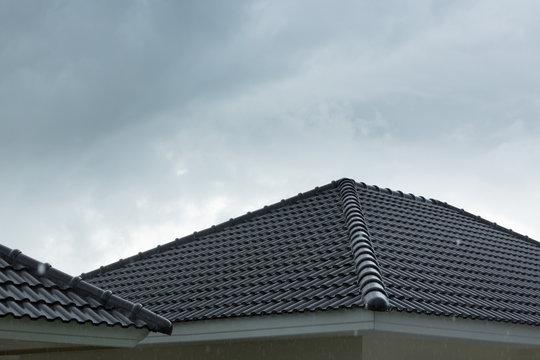 rain storm downpour on black roof tile of residential house