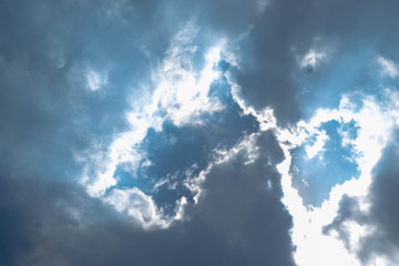Blue sky with white clouds and gray cloud blue sky on a bright day with white clouds coming in floating come to cover sun causes a white beam causing beauty in the sky.