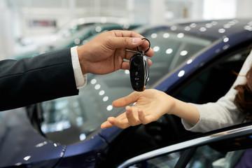 Salesman giving electronic car keys