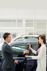 Salesman opening door for customer