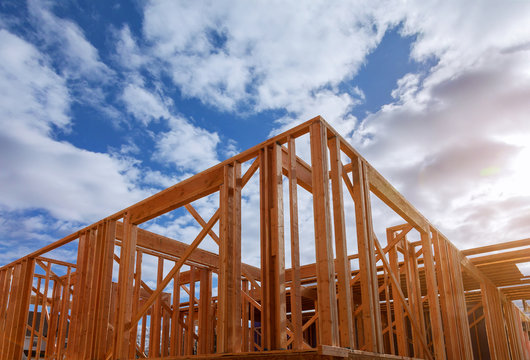 Close-up of beam built home under construction and blue sky with wooden truss, post and beam framework. Timber frame house, real estate background