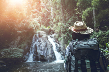 Rear view of young woman in hat with backpack standing in front of waterfall. Travel concept.