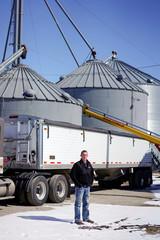 Soybean farmer Austin Rincker poses for a photograph near a grain truck and storage bins at his farm in Moweaqua Illinois