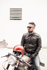 Guy posing with his motorcycle in an empty location.