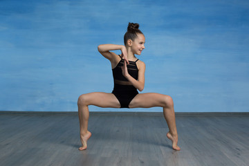 Girl athlete doing exercise gymnastics doing squats in the splits, hands in lock in front of you, head turned in profile on a blue background.