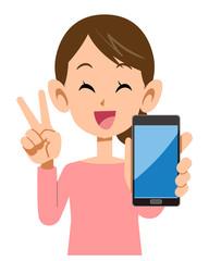 スマートフォンを手に持ちピースサインを示す女性