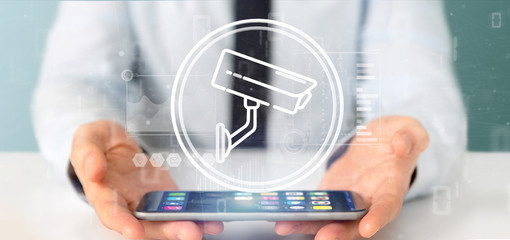 Businessman holding Security camera system icon and statistics data - 3d rendering