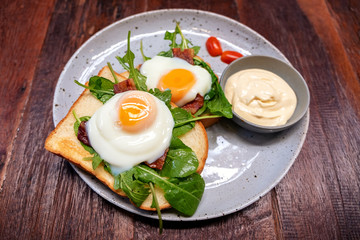 Breakfast sandwich with eggs, bacon and sour cream in a plate on wooden table