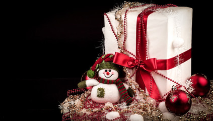 box with Christmas present and Christmas decorations on a black