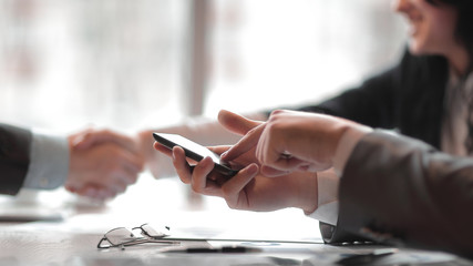 close up.a businessman uses a smartphone during a business meeting.