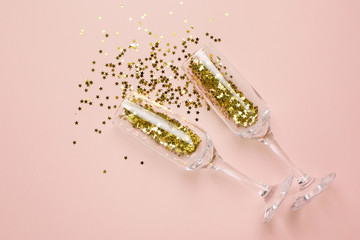 Champagne glasses with golden stars confetti on beige color paper background minimal style