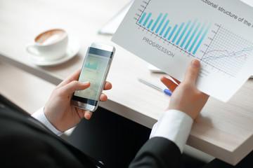 closeup.businessman checks the financial data using a smartphone