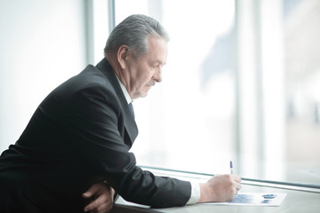 businessman signs a document, standing near the office window