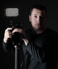 professional photographer with camera on tripod.isolated on black background