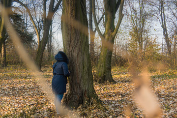 Girl at autumn in blue clothes exploring in the park