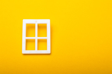 Plastic white window on yellow background with copy space for text.