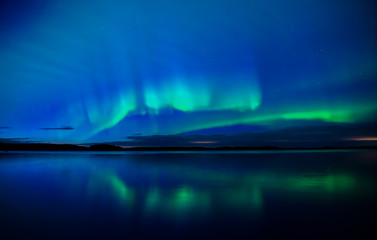 Wall Mural - Northern lights dancing over calm lake in Farnebofjarden national park in Sweden.