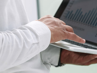 close up. a businessman uses a laptop to work with financial data.