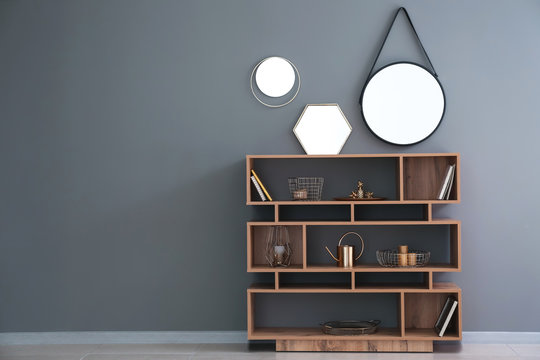 Wooden shelving unit with golden decor and mirrors on grey wall