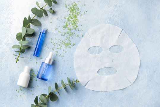 Sheet facial mask with cosmetic products on color background