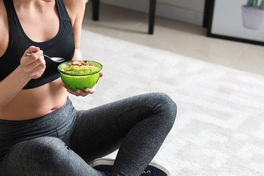 Sporty woman eating tasty yogurt at home