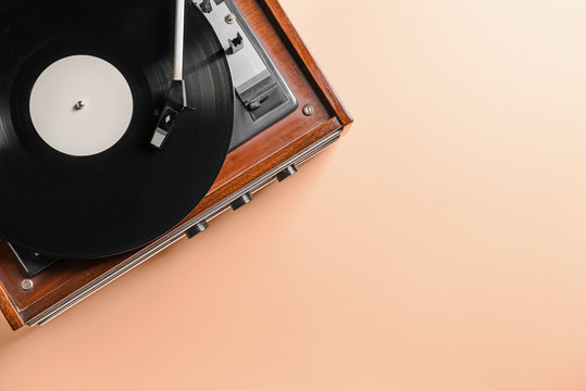 Record player with vinyl disc on color background