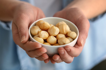 Woman holding bowl with peeled macadamia nuts, closeup