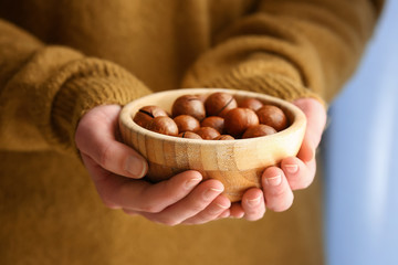 Woman holding bowl with macadamia nuts, closeup