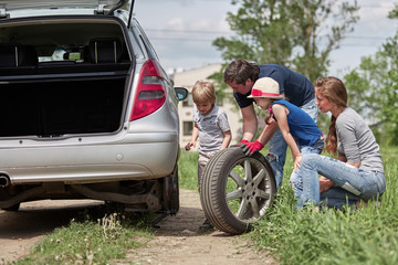 children help their father to replace the car tire.