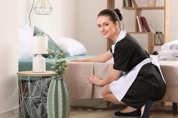 Beautiful female housekeeper making bed in room