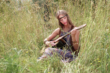 young hippie woman playing guitar sitting on forest glade