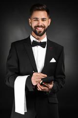 Handsome waiter with notebook on dark background
