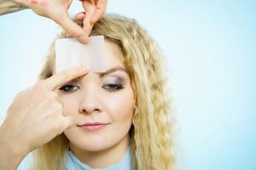 Woman using oil blotting tissues on model