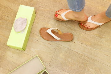 Unrecognizable woman trying on flip flops