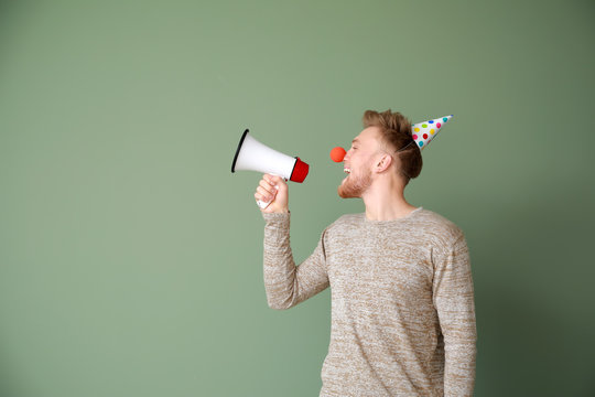 Funny man with megaphone on color background. April Fools' Day prank