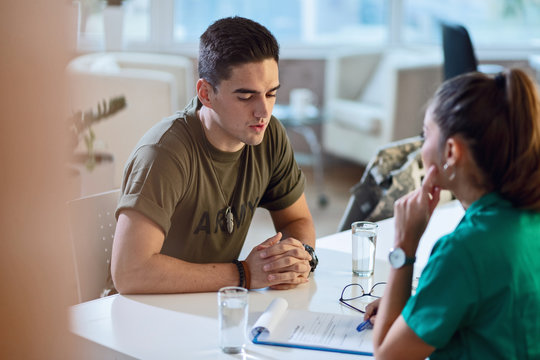 Young army soldier talking with doctor during his therapy.