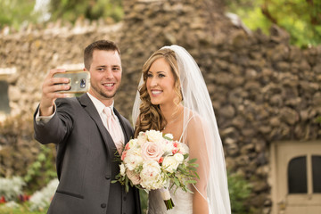 Young attractive bride and groom taking a selfie