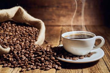 Fotobehang Cafe Czarna kawa na starych deskach i rozsypane ziarna