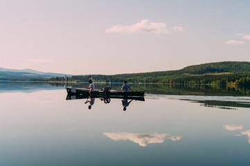 Zwei Paddler im Kanu auf spiegelglattem See in Schweden