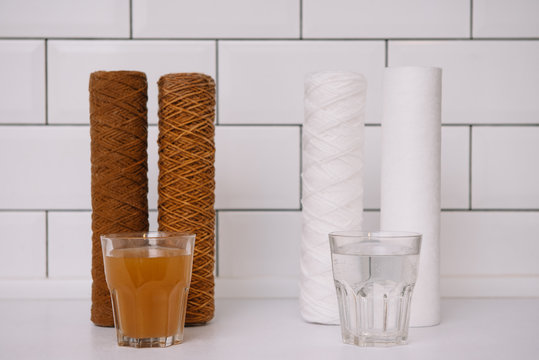 Water filter cartridge used and a glass of rusty water brown coloring and new filter and a glass of clean water. Evidence of contamination of tap water with iron cations. white kitchen