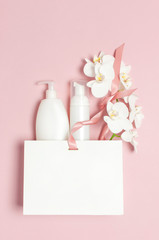 Flat lay top view White cosmetic bottle containers gift bag White Phalaenopsis orchid flowers on pink background. Cosmetics SPA branding mock-up Natural organic beauty product concept Minimalism style
