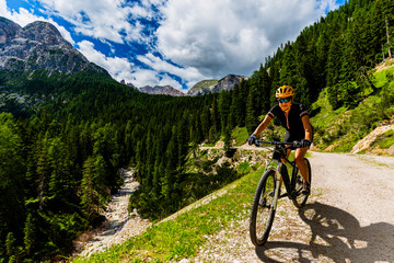 Wall Mural - Single mountain bike rider on electric bike, e-mountainbike rides up mountain trail. Man riding on bike in Dolomites mountains landscape. Cycling e-mtb enduro trail track. Outdoor sport activity.