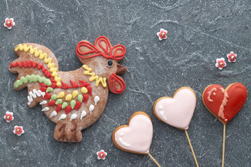 Gingerbreads shaped as a rooster bird and hearts on dark textured board.