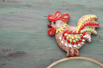 Gingerbreads shaped as a rooster bird and hearts on textured wood, text space