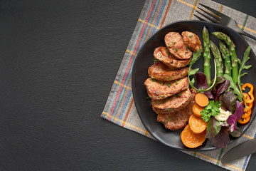 Fried slices of beef, sweet potato and mixed salad on black plate set for meal on dark slate, copy-space