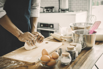 happy family in kitchen. Father and son knead dough and bake the bakery together