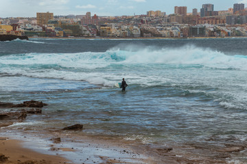 Tourism and travel. Windy day on the ocean. Surfer with a board. Canary Islands, Gran Canaria, Atlantic Ocean. Tropics. City of Las Palmas